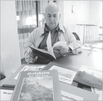 Friedhelm Theis mit einigen heimatkundlichen Bänden über Holzheim, an denen Karl Schughart und er gearbeitet haben.